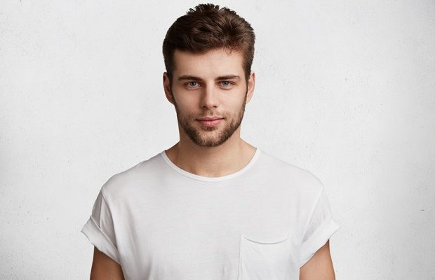 Serious confident young male student comes home after classes, dressed casually in white t shirt, waits for girlfriend, isolated over white background
